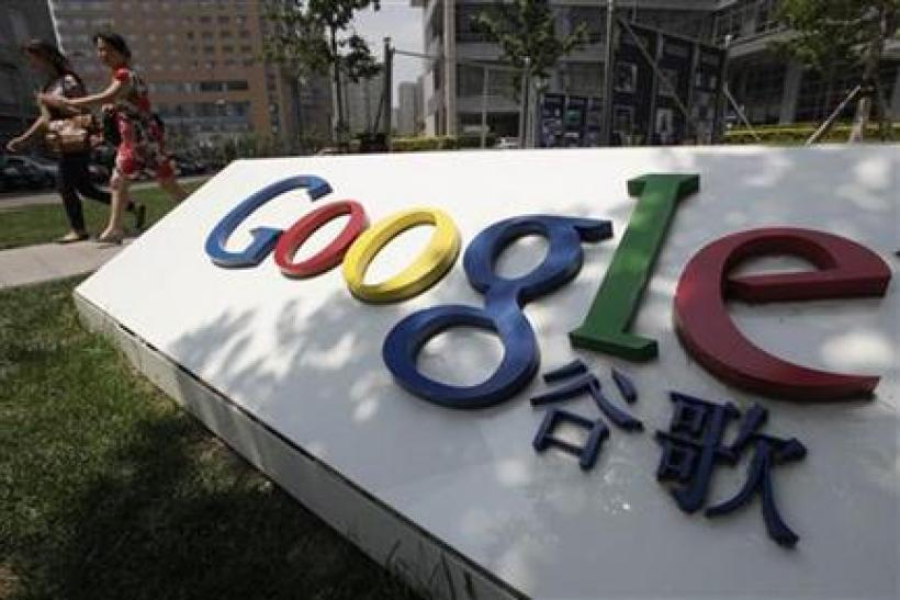 Women walk past the logo of Google in front of its former headquarters in Beijing