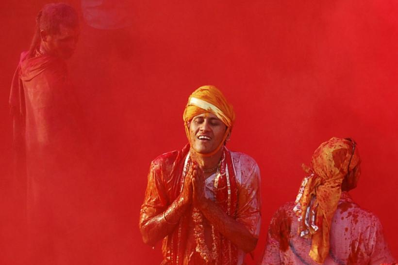 A man daubed in colours prays during Lathmar Holi celebrations at Nandgaon village