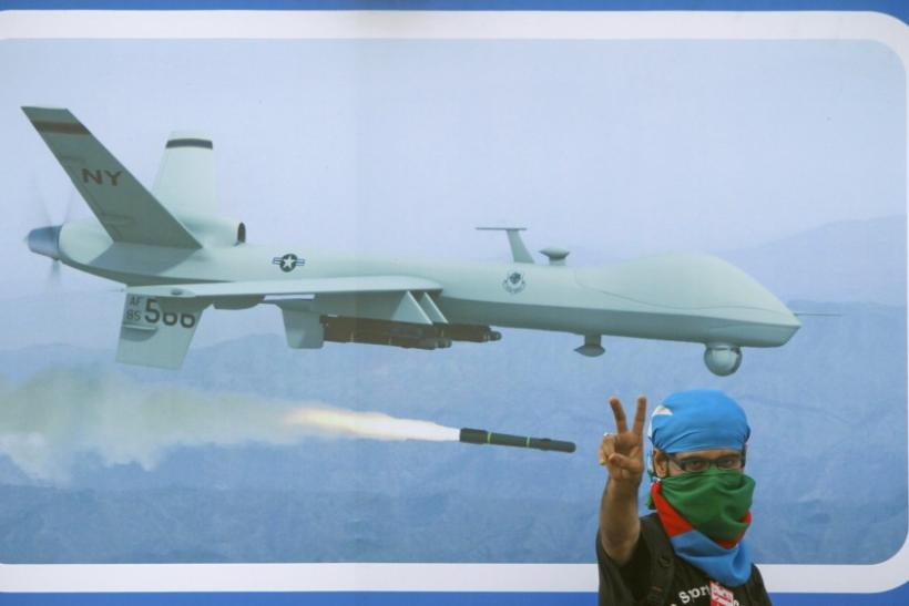 A supporter of religious and political party Jamaat-e-Islami flashes the victory sign in front of an image of drone, during a rally against drone attacks in Karachi