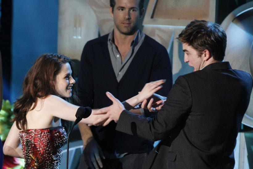 Robert Pattinson and Kristen Stewart accept the award for best kiss as presenter Ryan Reynolds watches at the 2011 MTV Movie Awards in Los Angeles, June 5, 2011.