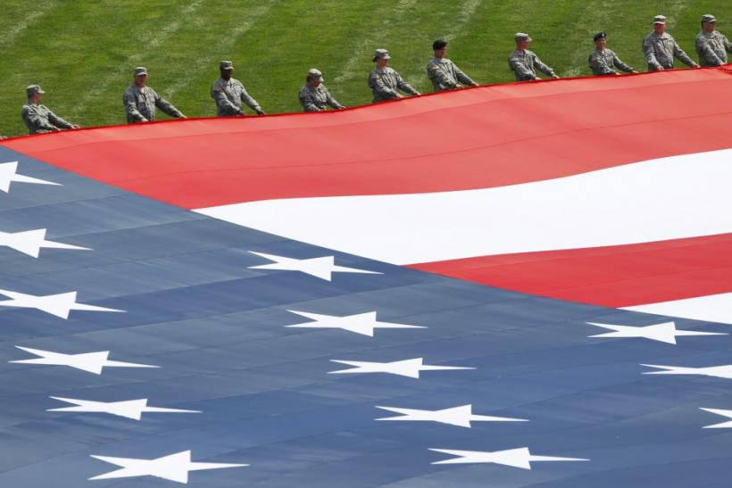 Military personnel open a giant American flag before the Indianapolis 500 auto race in Indianapolis