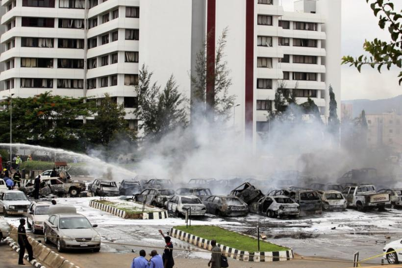 Members of the emergency services work at the scene of an explosion at a police station after a suspected suicide bomber was killed and many vehicles were destroyed inAbuja