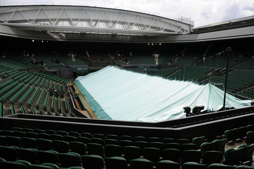 The covers are seen pulled across Centre Court during rainy weather on the day before the start of the 2011 Wimbledon tennis championships in London.