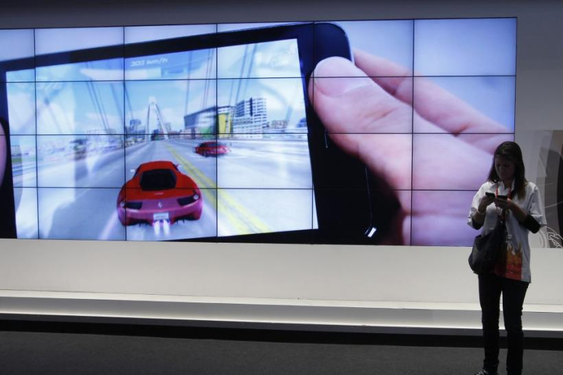 A visitor uses her mobiles while standing in front of a big screen displaying an Android tablet from Samsung