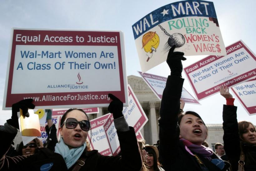 Women protesters hold signs in front of the Supreme Court