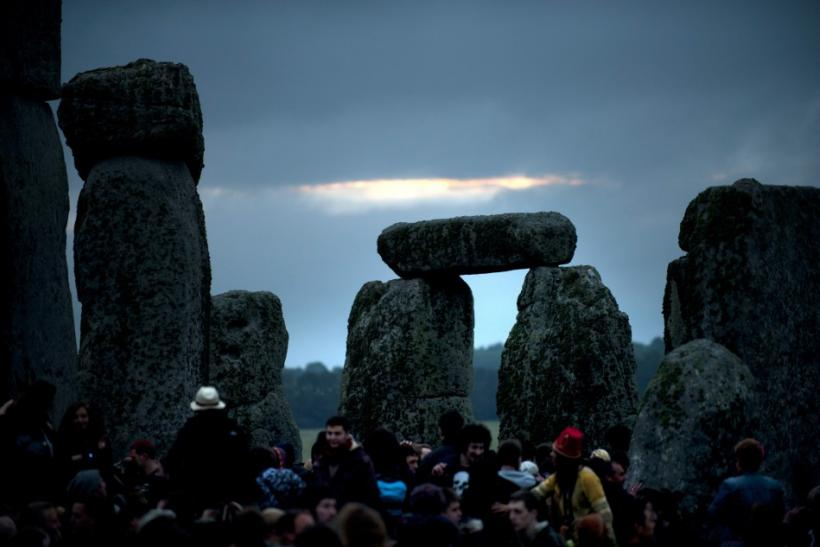 Revellers surround the ancient Stonehenge monument as the sun rises