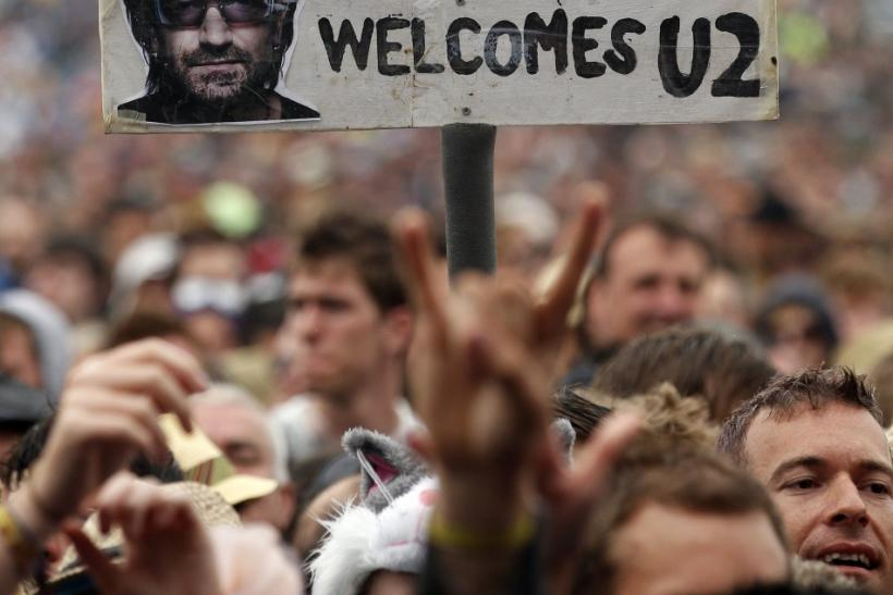 A festival goer holds a placard protesting against Irish group U2