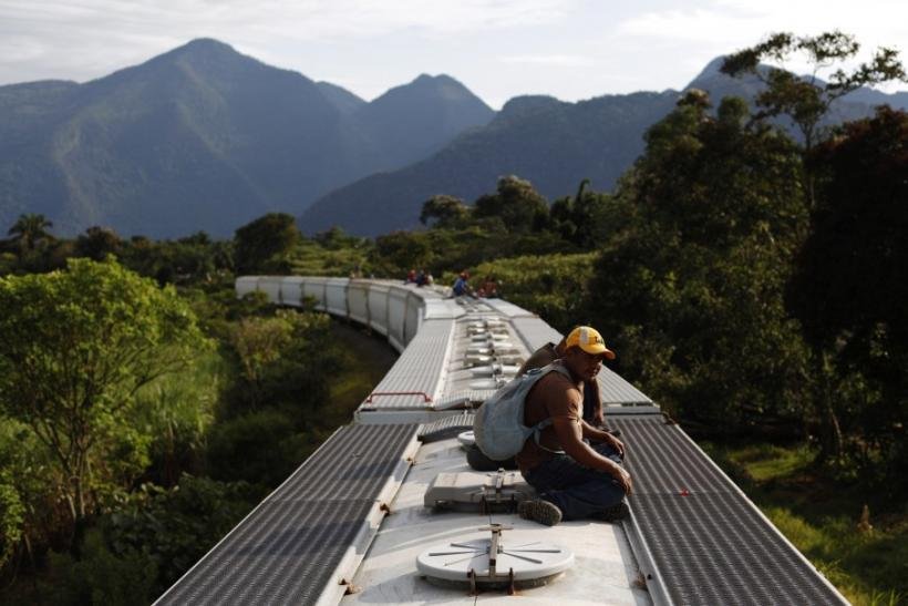 Honduran immigrants ride on the top of a freight train