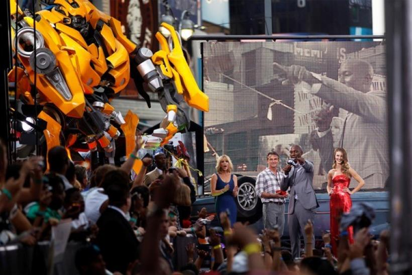 """Cast member Tyrese Gibson addresses the crowd in front of Rosie Huntington-Whiteley during the premiere of """"Transformers: Dark of The Moon"""" in Times Square in New York"""