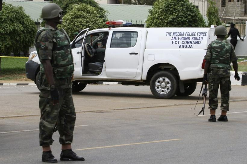 Soldiers take up positions near the scene of an explosion at a police station in Abuja