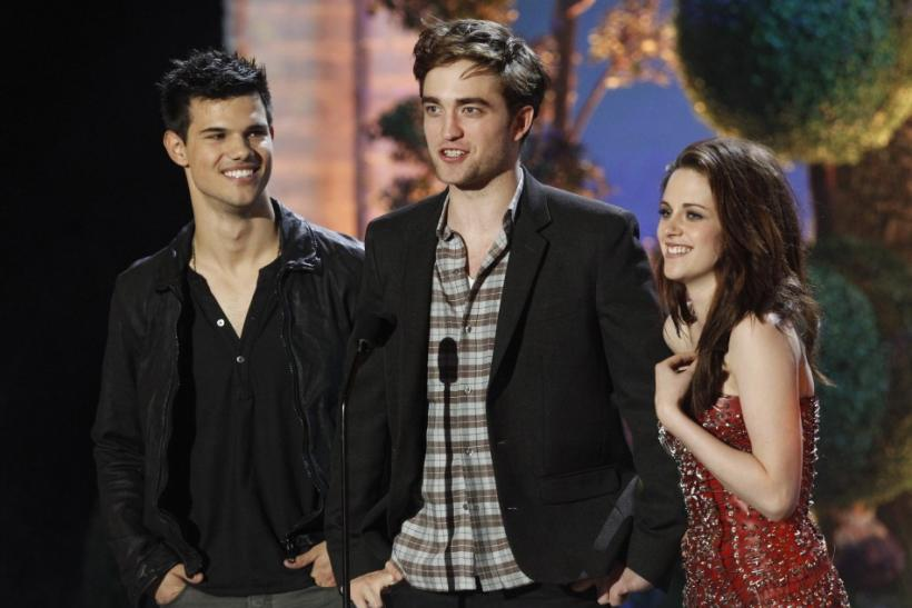 "Taylor Lautner (L), Robert Pattinson and Kristen Stewart introduce a clip from ""The Twilight Saga: Breaking Dawn"" at the 2011 MTV Movie Awards in Los Angeles, June 5, 2011."