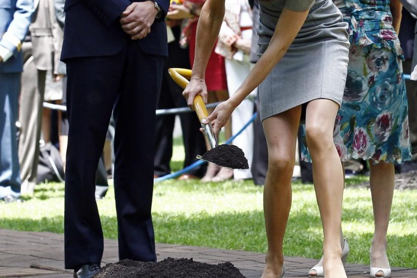 Britain's Prince William watches as his wife Catherine, Duchess of Cambridge, shovels dirt during a tree planting ceremony at Rideau Hall in Ottawa