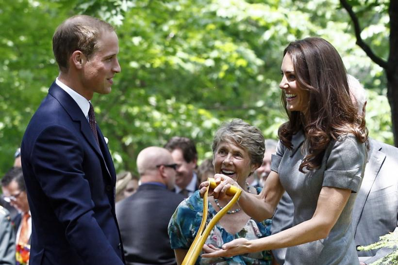 Britain's Prince William hands his wife Catherine, Duchess of Cambridge, a shovel during a tree planting ceremony at Rideau Hall in Ottawa