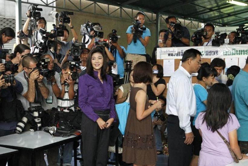 Puea Thai Party's PM candidate Yingluck Shinawatra waits in line for her turn to vote
