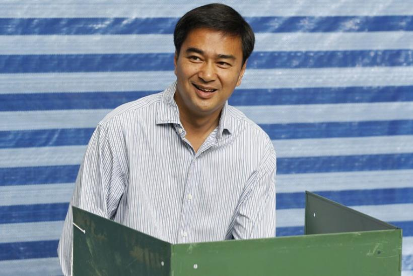 Thai Prime Minister Abhisit Vejjajiva (C) of the ruling Democrat Party smiles as he votes at a polling station in Bangkok
