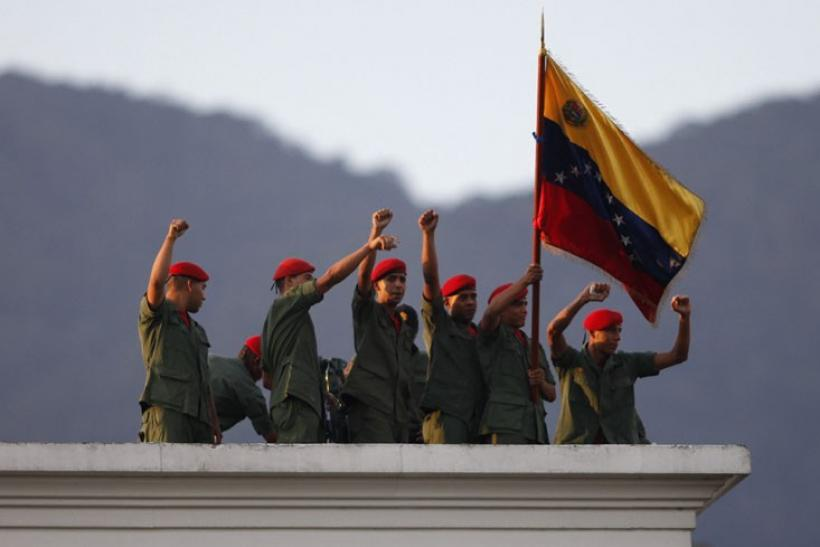 Venezuelan soldiers greet President Hugo Chavez from a rooftop