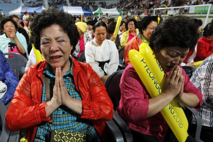 South Koreans react as they hear that Pyeongchang would win in a first round of voting for the 2018 Winter Olympics Games in Pyeongchang, at a ski jump stadium in Pyeongchang
