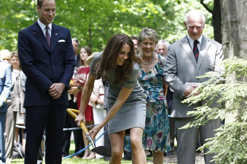Britain's Prince William watches as his wife Catherine, Duchess of Cambridge, shovels dirt