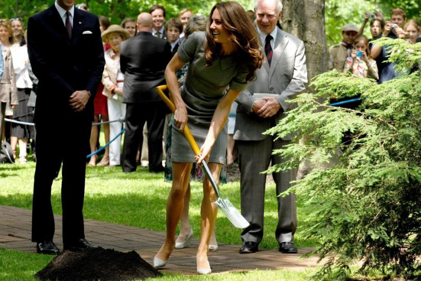 Britain's Prince William (L) watches as his wife Catherine, Duchess of Cambridge wields a shovel