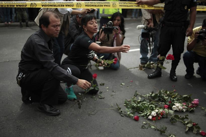 People place flowers in honor of Facundo Cabral at the crime scene where the Argentine singer was shot dead in Guatemala