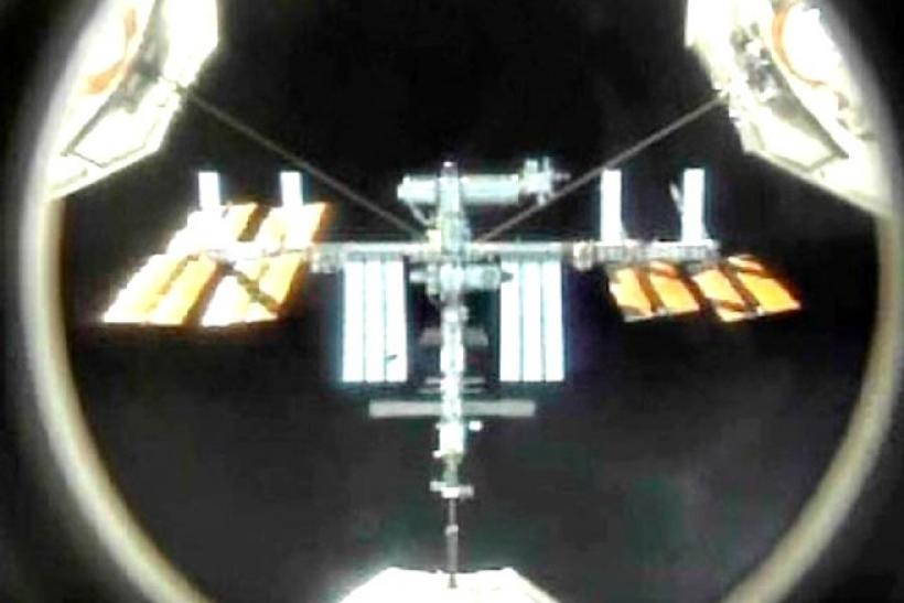 The International Space Station is seen in the crosshairs of the mating adapter mounted in the space shuttle Atlantis' payload bay