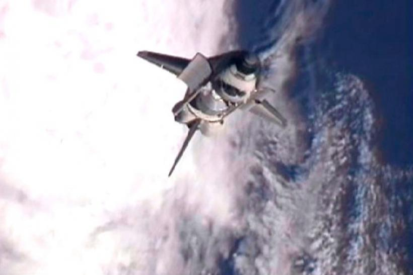 The space shuttle Atlantis goes through a backflip rotation to expose the heat shield to International Space Station crew members