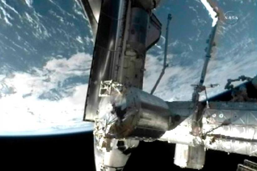 The space shuttle Atlantis is seen docked to the International Space Station with the earth in the background