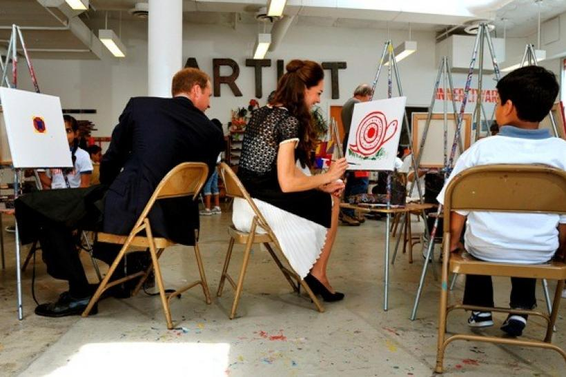 Britain's Catherine, the Duchess of Cambridge, giggles as Prince William comments on her artistic skills during a visit to the Inner-City Arts club in Los Angeles