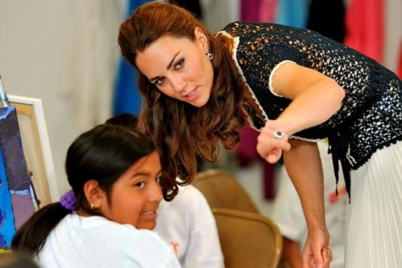 Britain's Catherine, the Duchess of Cambridge, talks to children as she and Prince William tour the art room during a visit to the Inner-City Arts club in Los Angeles