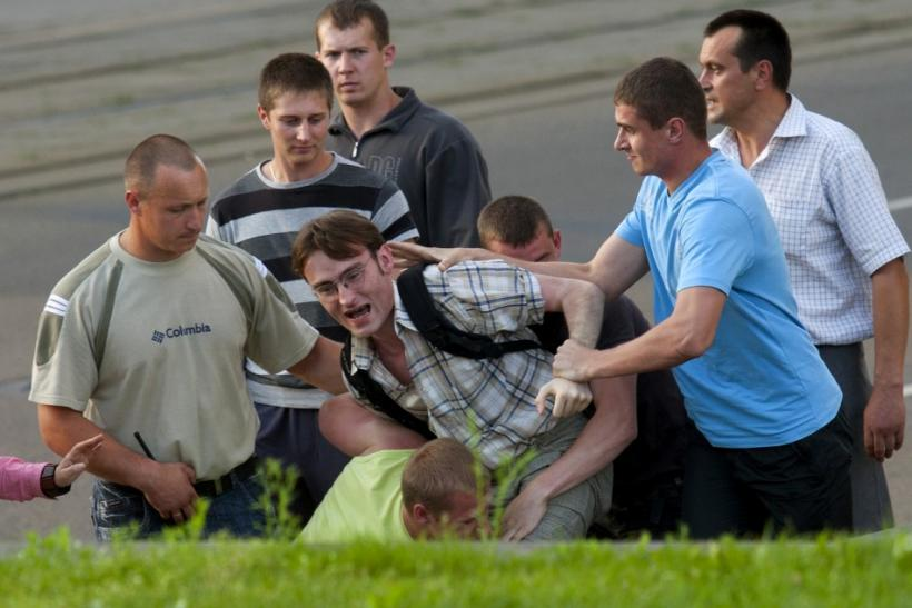 Belarusian policemen in plainclothes detain a man