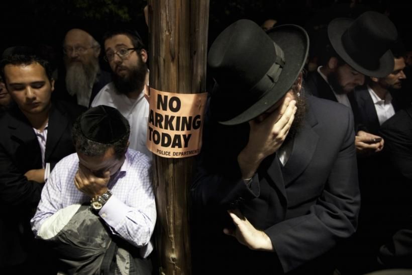 Men weep while listening to the funeral of Leibby Kletzky outside a synagogue in the Brooklyn borough of New York