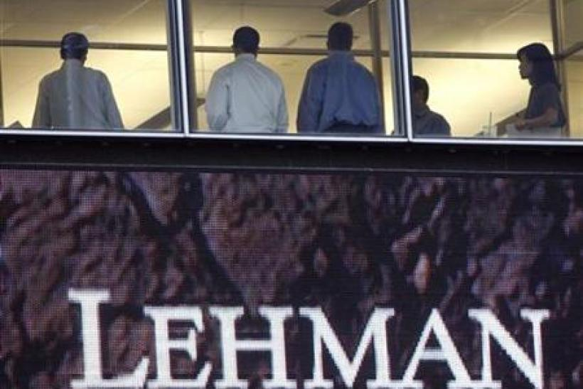 People stand next to windows, above animated sign, at Lehman Brothers headquarters in New York