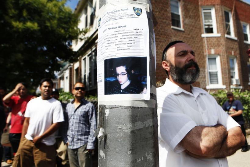 People stand near the home of the suspected killer of Kletzky in the Orthodox Jewish section of Borough Park in the Brooklyn borough of New York