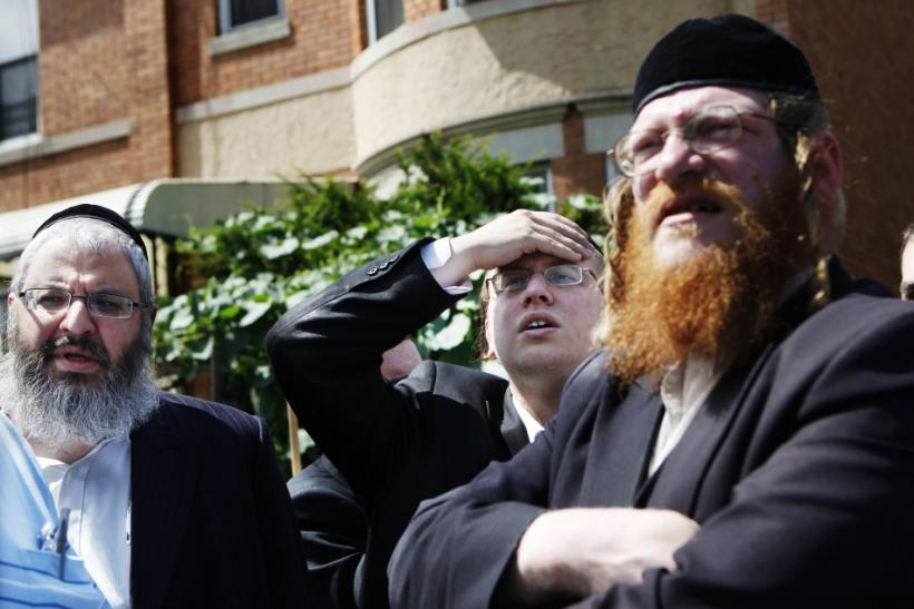 Men stand near the home of the suspected killer of Kletzky in the Orthodox Jewish section of Borough Park in the Brooklyn borough of New York