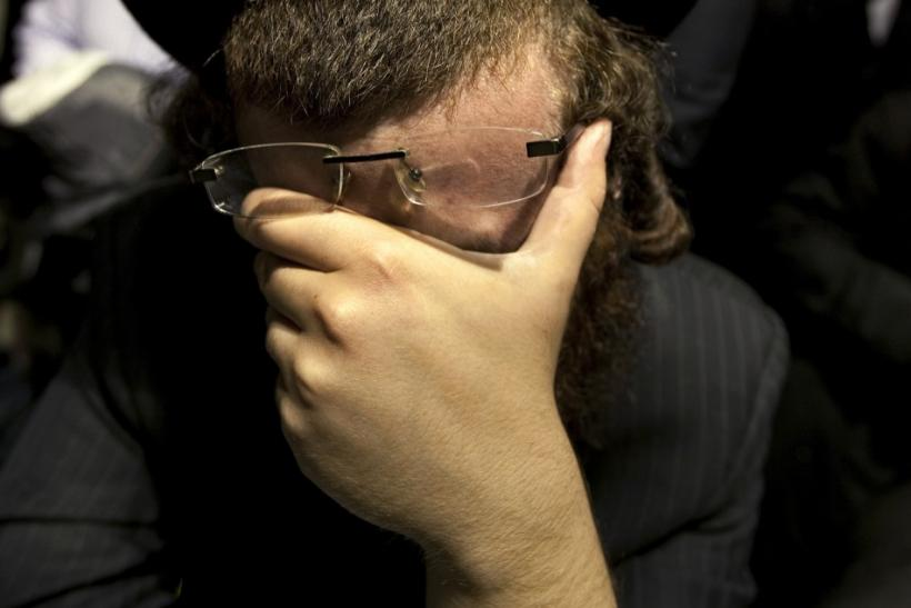 A man weeps while listening to the funeral of Leiby Kletzky in the Brooklyn borough of New York