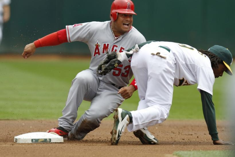 Los Angeles Angels' Bobby Abreu is tagged out by Oakland Athletics' Jemile Weeks while attempting to steal second base in the first inning of the first game of their MLB American League baseball doubleheader in Oakland, California