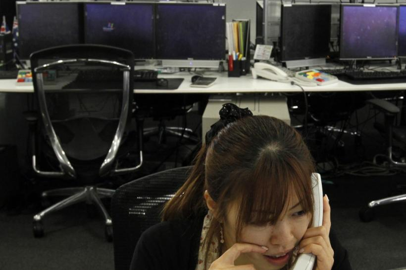 An employee talks on a phone at a foreign currency trading company in Tokyo