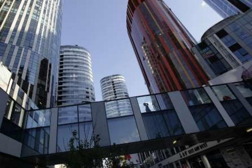 A woman walks between buildings at Sanlitun SOHO residential and commercial complex in Beijing