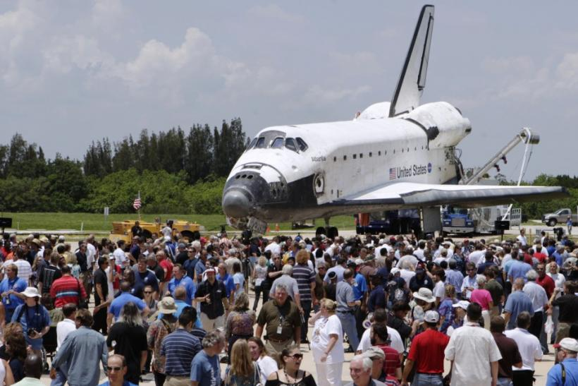 Space center workers gather for an event held near the space shuttle Atlantis after it was towed near its hangar after landing at the Kennedy Space Center in Cape Canaveral, Florida