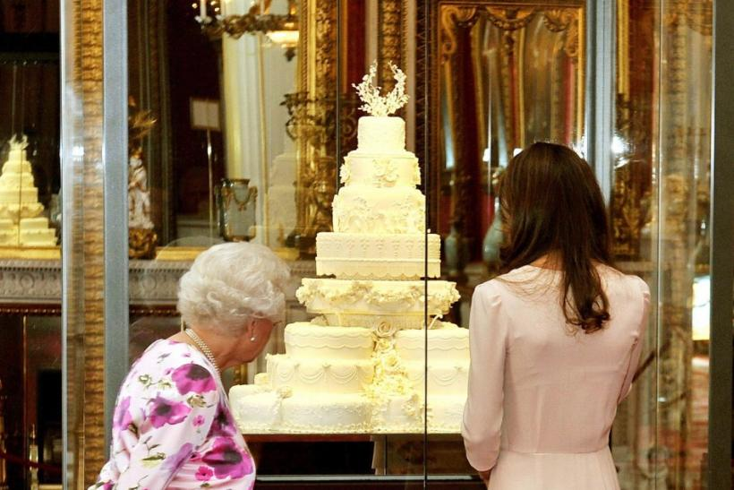 Britain's Queen Elizabeth (L) and Catherine, the Duchess of Cambridge, look at the part original, part replica royal wedding cake made for the wedding of Britain's Prince William and Kate Middleton, as they view the summer exhibition at Buckingh