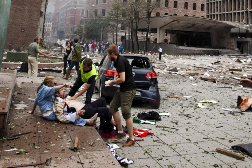 An injured man is attended to at the site of a powerful explosion that rocked central Oslo