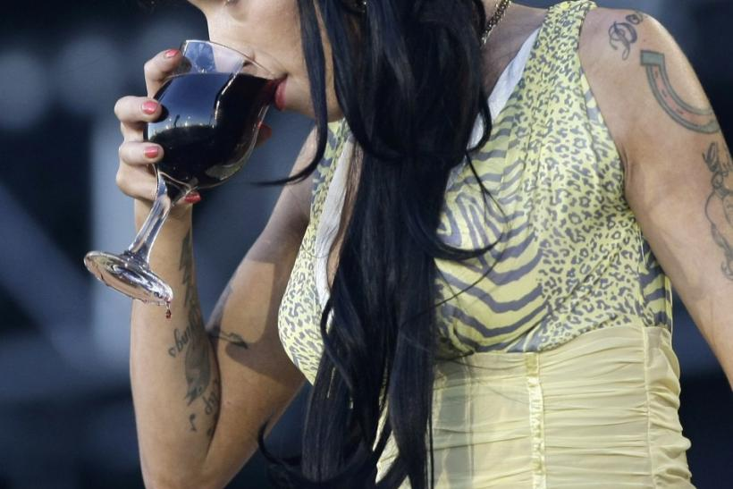 Winehouse drinking her 8th glass of wine onstage