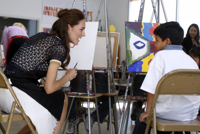 Kate Middleton talks with a child as she sits down to paint a picture during a tour of the Inner City Arts campus in Los Angeles