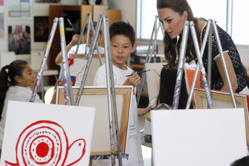 Kate Middleton observes a child as he paints a picture during a tour of the Inner City Arts campus in Los Angeles