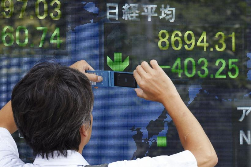 A man takes a picture of a stock index board with his mobile phone outside a brokerage in Tokyo