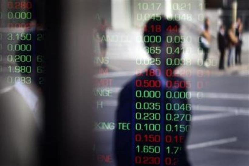Man is reflected in a window as he walks past the indicator boards at the Australian Stock Exchange in Sydney