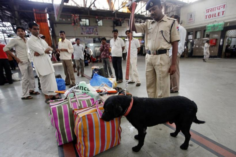 A Railway Protection Force officer uses a sniffer dog to check bags at the Chhatrapati Shivaji railway station in Mumbai