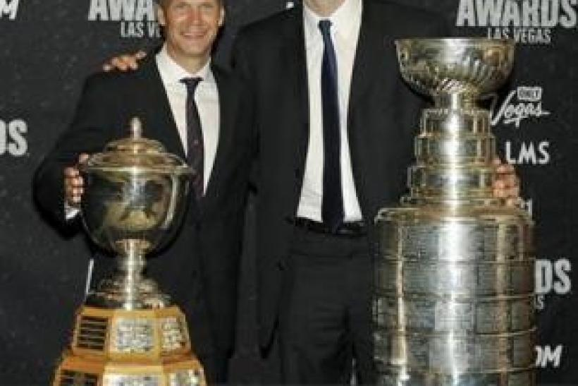 Detroit Red Wings' Nicklas Lidstrom (L) and Boston Bruins Zdeno Chara pose with the James Norris Memorial Trophy (L) and the Stanley Cup at the 2011 NHL Awards in Las Vegas