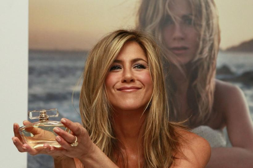 U.S. actress Jennifer Aniston poses with her fragrance 'Jennifer Aniston' during its launch at Harrods in London