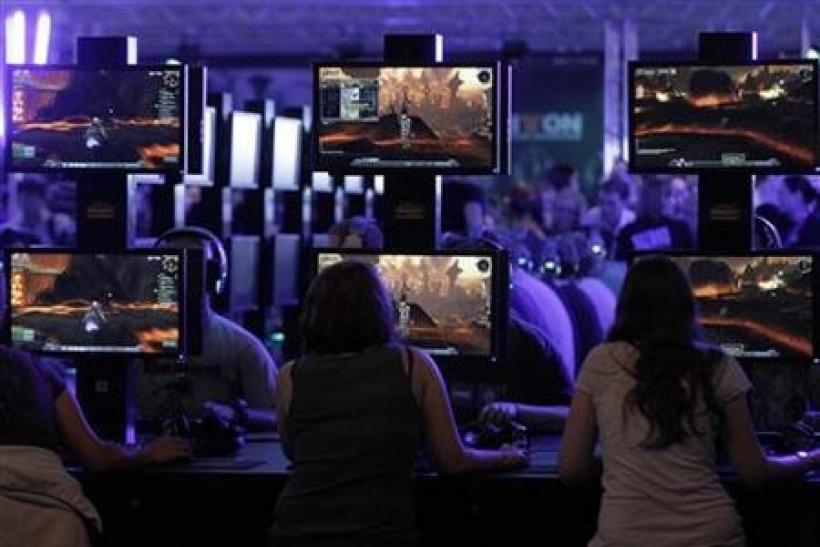 Visitors play ''World of Warcraft'' at an exhibition stand during the Gamescom 2011 fair in Cologne